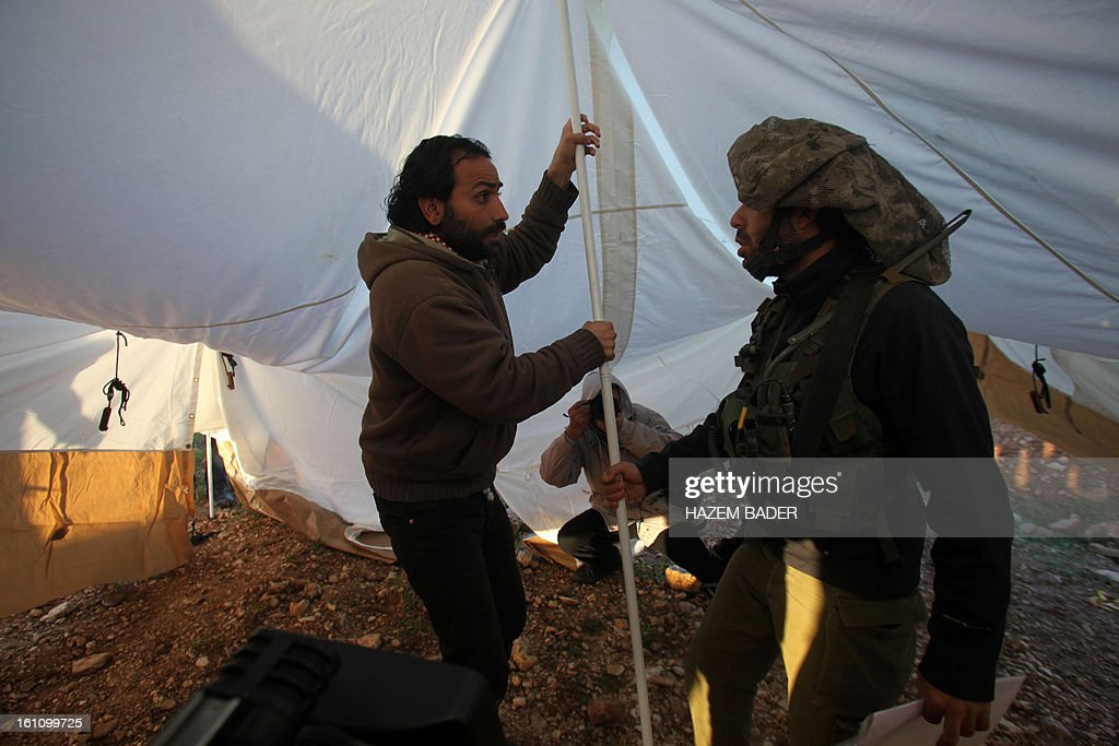 A Palestinian activist is stopped by an Israeli oldier as he takes part in the settlement of a new encampment to protest against settlement building in the Yatta, south of the West Bank city of Hebron on February 9, 2013. Soldiers dismantled tents that were being erected in two different areas near the town of Yatta, and forced activists to leave, the Palestinian witnesses said. BADER
