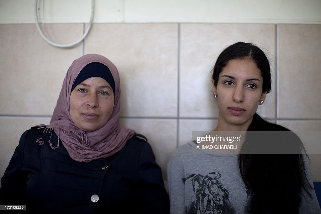 Palestinian activist Nariman a-Tamimi (L) and Rana Hamadah (R) sit for the verdict during their trial at Israel's Ofer military court near the West Bank city of Ramallah on July 9, 2013. The two women were arrested on 28 June during a weekly rally in a West Bank village and charged with entering a closed military zone.