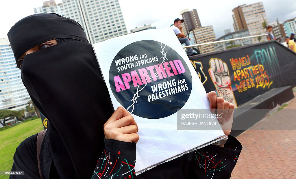 A Palestinian activist, wearing a full face veil, holds a sign during a protest against Israel at the north beach in Durban on March 10, 2013 ahead of the Israeli Apartheid Week (IAW) from March 11 to 17, 2013 in South Africa. The annual international series of events includes rallies, lectures, cultural performances, film screenings, multimedia displays and boycott of Israel actions held in cities and campuses across the globe.
