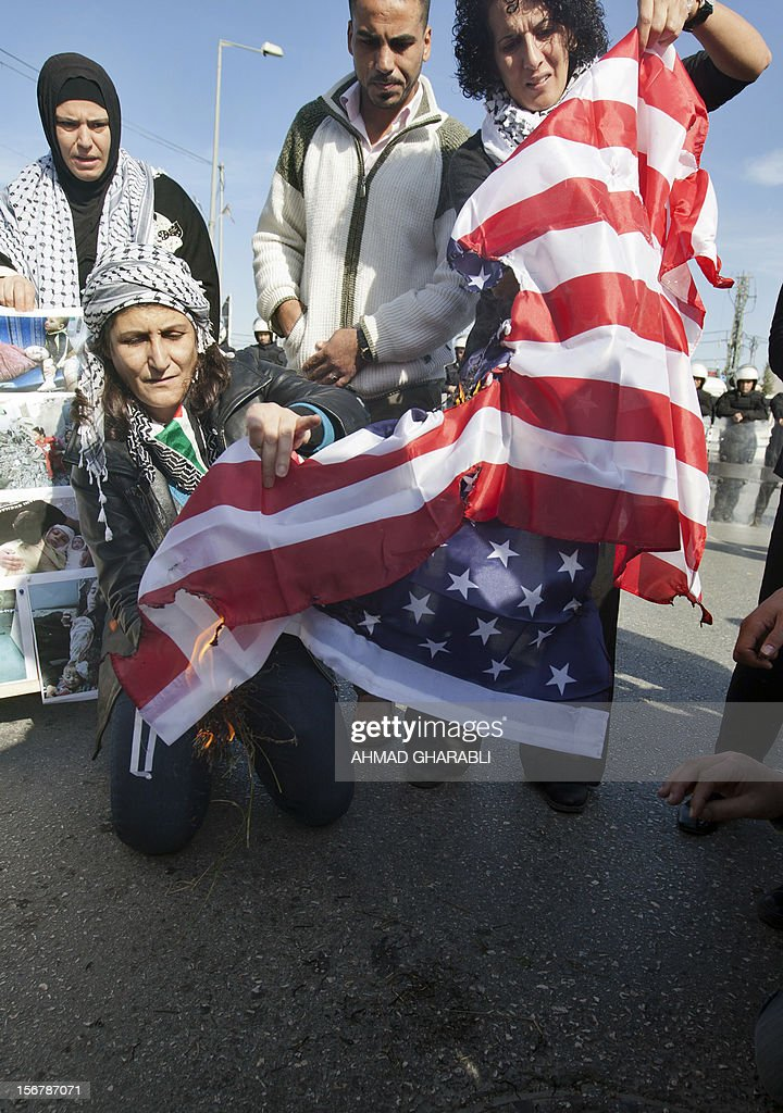 Palestinian activists burn the American flag during a demonstration against US Secretary of State Hillary Clinton's visit in the West Bank city of Ramallah on November 21, 2012. US Secretary of State Hillary Clinton expressed 'rock solid' support for Israel's security while calling for a de-escalation of the conflict in Gaza where fighting entered its eighth day, despite signs of an emerging truce.