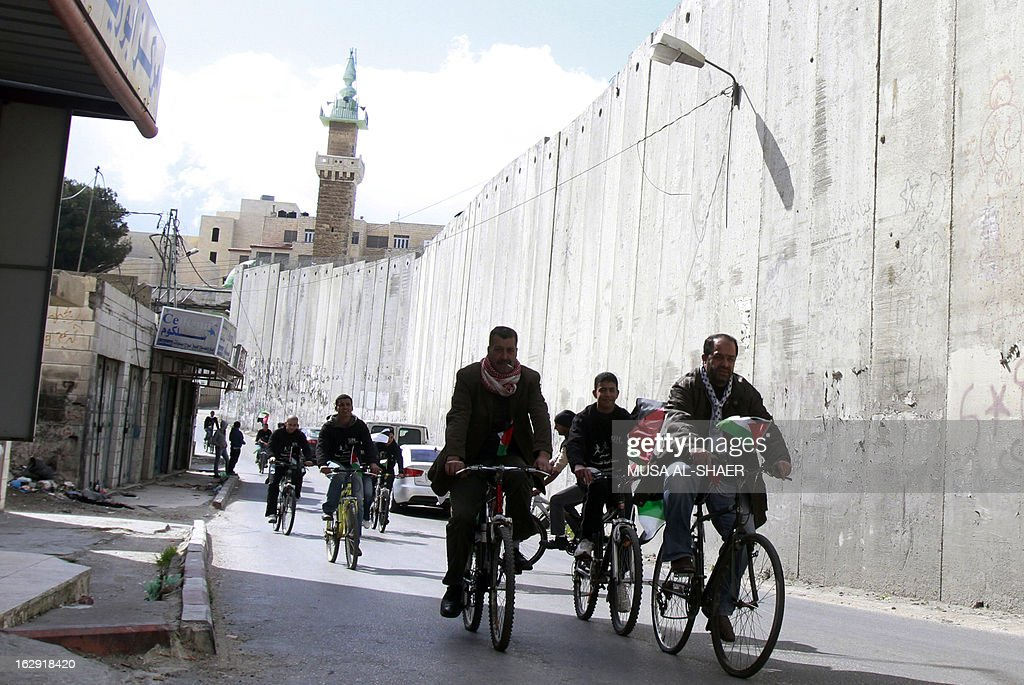 Palestinian activists demonstrate on their bicycles as they ride along Israel's controversial separation barrier in Azariya separated from Jerusalem by the concrete barrier as they protest against Jerusalem's third annual marathon which takes the runners past the Israeli settlement of Maale Adumim, in the Israeli-occupied West Bank, on March 1, 2013. In a non-binding 2004 judgment, the International Court of Justice called for the dismantling of all parts of the separation barrier built on Israeli occupied Palestinian territory.