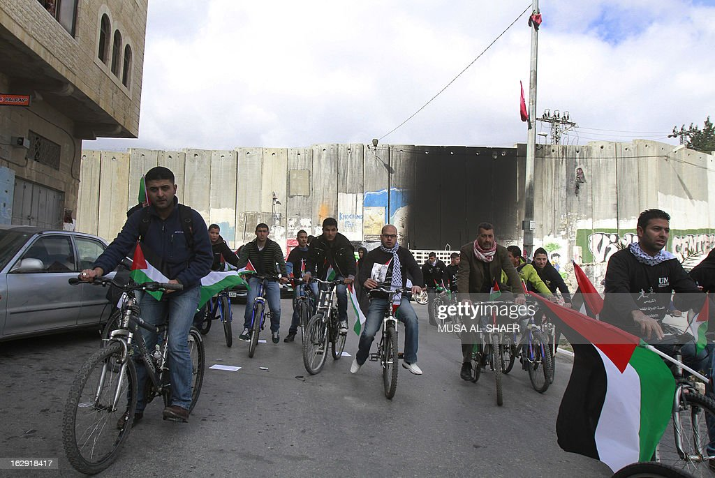 Palestinian activists demonstrate on their bicycles decorated with the Palestinian flag near Israel's controversial separation barrier in Azariya separated from Jerusalem by the concrete barrier as they protest against Jerusalem's third annual marathon which takes the runners past the Israeli settlement of Maale Adumim, in the Israeli-occupied West Bank, on March 1, 2013. In a non-binding 2004 judgment, the International Court of Justice called for the dismantling of all parts of the separation barrier built on Israeli occupied Palestinian territory.