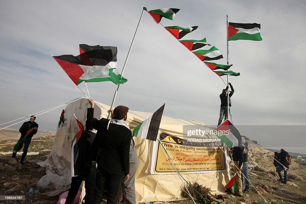 Palestinian activists fix flags on a tent in an 'outpost' named Bab al-Shams ('Gate of the Sun') that they set up between Jerusalem and the Jewish settlement of Maale Adumim in the Israeli-occupied West Bank, in an area where Israel has vowed to build new settler homes, on January 12, 2013. The Israeli occupation administration gave Palestinian activists an ultimatum to quit the protest camp in part of the West Bank, but hours after the deadline passed, there was no sign of any Israeli move to evict the protesters. AFP PHOTO/ABBAS MOMANI