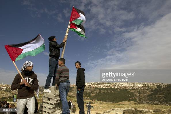 Palestinian activists fixes a flag over confiscated lands by Israeli army on January 25 2013 in the West Bank village of Beit Iksa Activists said...