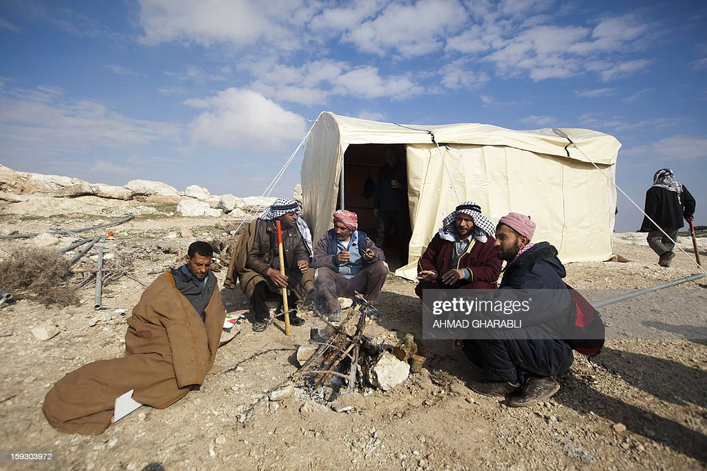 Palestinian activists make a fire nest to a tent they set up on January 11, 2013 at an 'outpost' named Bab al-Shams ('gate of the sun') in the Israeli-occupied West Bank , between Jerusalem and the Jewish settlement of Maale Adumim (background), in an area Israel said it would build thousands of new settler homes. Six weeks ago, Israel announced plans to build thousands of settler homes in the largely uninhabited E1 area, in a move which sparked a global outcry. E1 falls within Area C of the West Bank which is under full Israeli civilian and security control and where Palestinians find it almost impossible to obtain building permits.