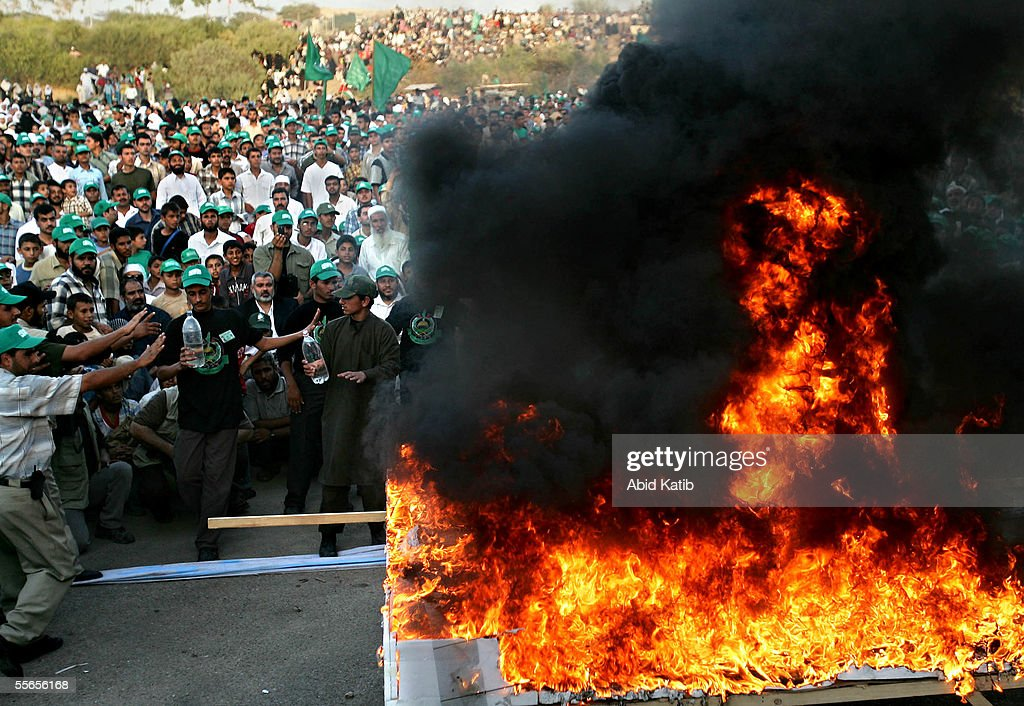 Palestinian activists of the Islamic Resistance Movement Hamas burn a model of an Israeli settlement during a celebration rally of the Israeli...