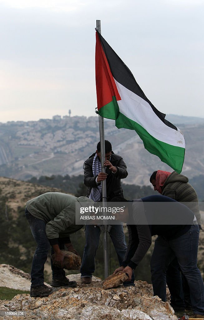 Palestinian activists put up their national flag on January 11, 2013 at an 'outpost' they set up named Bab al-Shams ('gate of the sun') in the Israeli-occupied West Bank , between Jerusalem and the Jewish settlement of Maale Adumim, in an area Israel said it would build thousands of new settler homes. Six weeks ago, Israel announced plans to build thousands of settler homes in the largely uninhabited E1 area, in a move which sparked a global outcry. E1 falls within Area C of the West Bank which is under full Israeli civilian and security control and where Palestinians find it almost impossible to obtain building permits. AFP PHOTO/ABBAS MOMANI