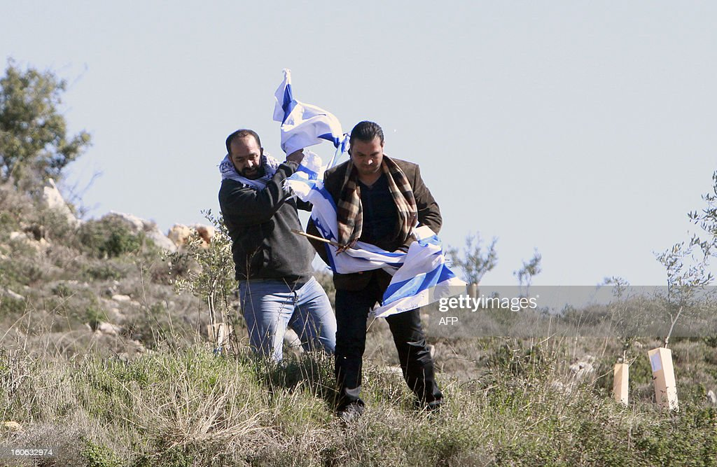 Palestinian activists remove Israeli flags during a protest against what they say is Israel's denial of access to their farmland, in the village of Khirbet Zakaria, near the settlement bloc of Gush Etzion, on February 4, 2013.