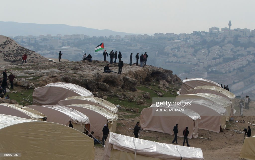 Palestinian activists set up on January 11, 2013 an 'outpost' named Bab al-Shams ('gate of the sun') in the Israeli-occupied West Bank , between Jerusalem and the Jewish settlement of Maale Adumim (background), in an area Israel said it would build thousands of new settler homes. Six weeks ago, Israel announced plans to build thousands of settler homes in the largely uninhabited E1 area, in a move which sparked a global outcry. E1 falls within Area C of the West Bank which is under full Israeli civilian and security control and where Palestinians find it almost impossible to obtain building permits.