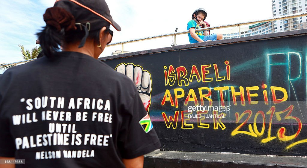 Palestinian activists stand infront of a graffiti as they participate in a protest against Israel at the north beach in Durban on March 10, 2013 ahead of the Israeli Apartheid Week (IAW) from March 11 to 17, 2013 in South Africa. The annual international series of events includes rallies, lectures, cultural performances, film screenings, multimedia displays and boycott of Israel actions held in cities and campuses across the globe. AFP PHOTO / RAJESH JANTILAL