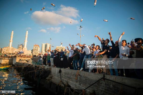 TOPSHOT Palestinian activists throw bottles into the sea containing messages against the siege of the Gaza Strip at the port in Gaza City on August...