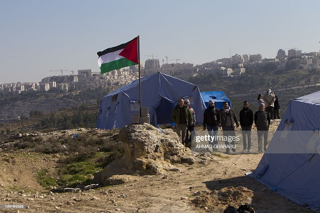 Palestinian activists walk past a flag and tents in the newly erected encampment set up to protest against Israel's intention to confiscate land on January 20, 2013 in the West Bank village of Beit Iksa. Activists say the Israeli army recently announced it would confiscate over 500 dunams (124 acres, 50 hectares) of land by the village, located on the northwestern outskirts of Jerusalem. AFP PHOTO/AHMAD GHARABLI