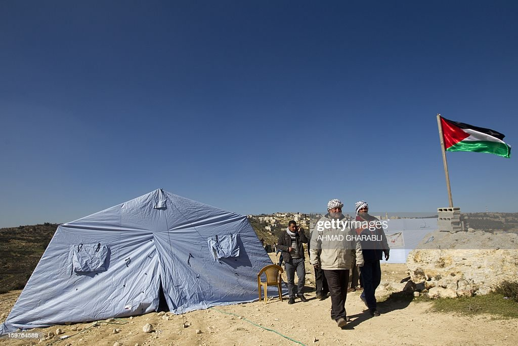 Palestinian activists walk past a flag and tents in the newly erected encampment set up to protest against Israel's intention to confiscate land on January 20, 2013 in the West Bank village of Beit Iksa. Activists say the Israeli army recently announced it would confiscate over 500 dunams (124 acres, 50 hectares) of land by the village, located on the northwestern outskirts of Jerusalem. On the background is seen the Israeli settlement of Ramot. AFP PHOTO/AHMAD GHARABLI