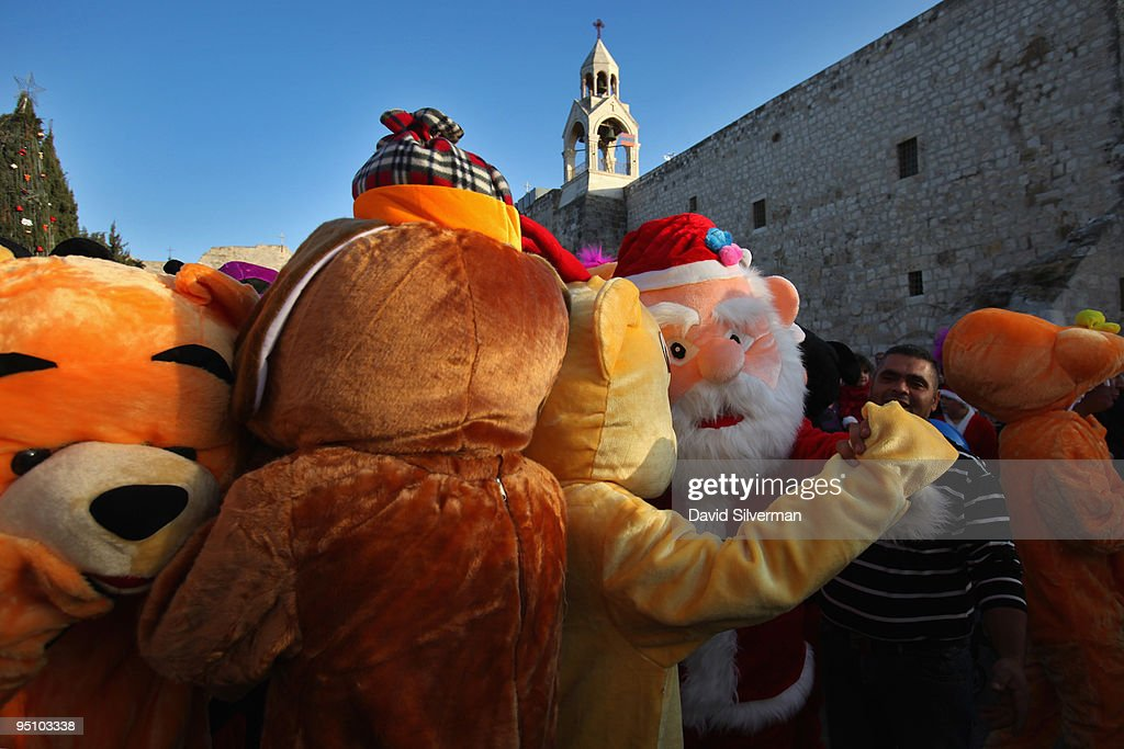 Palestinian actors dressed as cartoon characters dance as they entertain local children during preChristmas festivities in Manger Square by the...