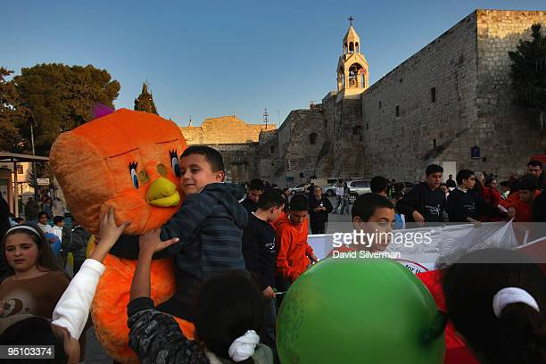 Palestinian actors dressed as cartoon characters play with local children during preChristmas festivities through Manger Square by the Church of the...
