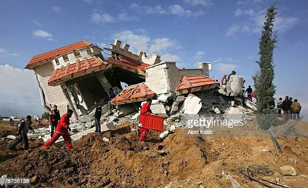Palestinian ambulance staff search for casualties through the rubble of a house destroyed by Israeli bulldozers and tanks on January 3 2008 at Khan...