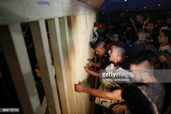 Palestinian and ArabIsraeli protestors push a gate during a demonstration against administrative detention and in support of Palestinian prisoner...