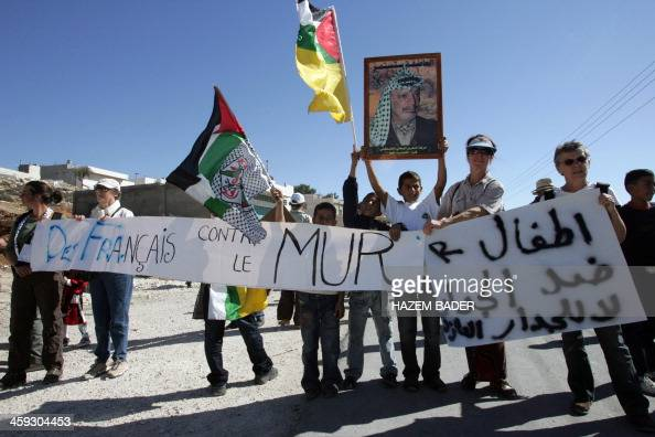 Palestinian and foreign activists hold a picture of late Palestinian leader Yasser Arafat and wave the Palestinian flag during a demonstration...