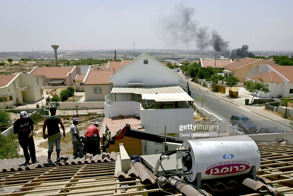 Palestinian and Israeli workers remove roof tiles as they dismantle Yaakov Biton home August 3 2005 in the northern Gaza Strip settlement of Nissanit...