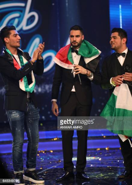 CORRECTION Palestinian Arab Idol TV show winner Yaacoub Shahin and Season 2 winner Mohammad Assaf stand with Amir Dandan on stage during the final in...
