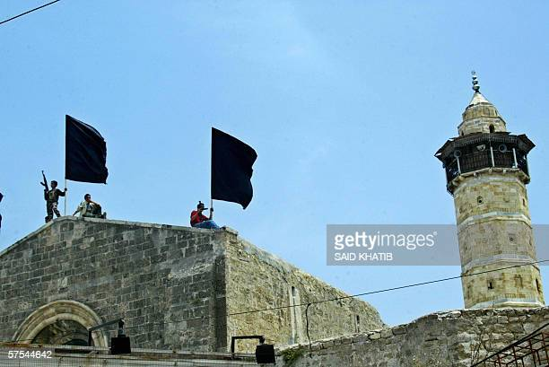Palestinian armed youths hold up black flags on the roof of Gaza City's AlOmari mosque during the funeral 06 May 2006 of five militants killed...