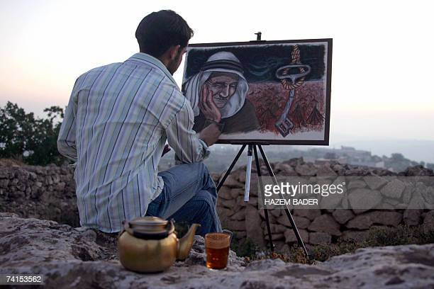 Palestinian artist Muaath alJaabari puts the finishing touches to his painting depicting an old man with tears in his eyes siting near tenets of a...