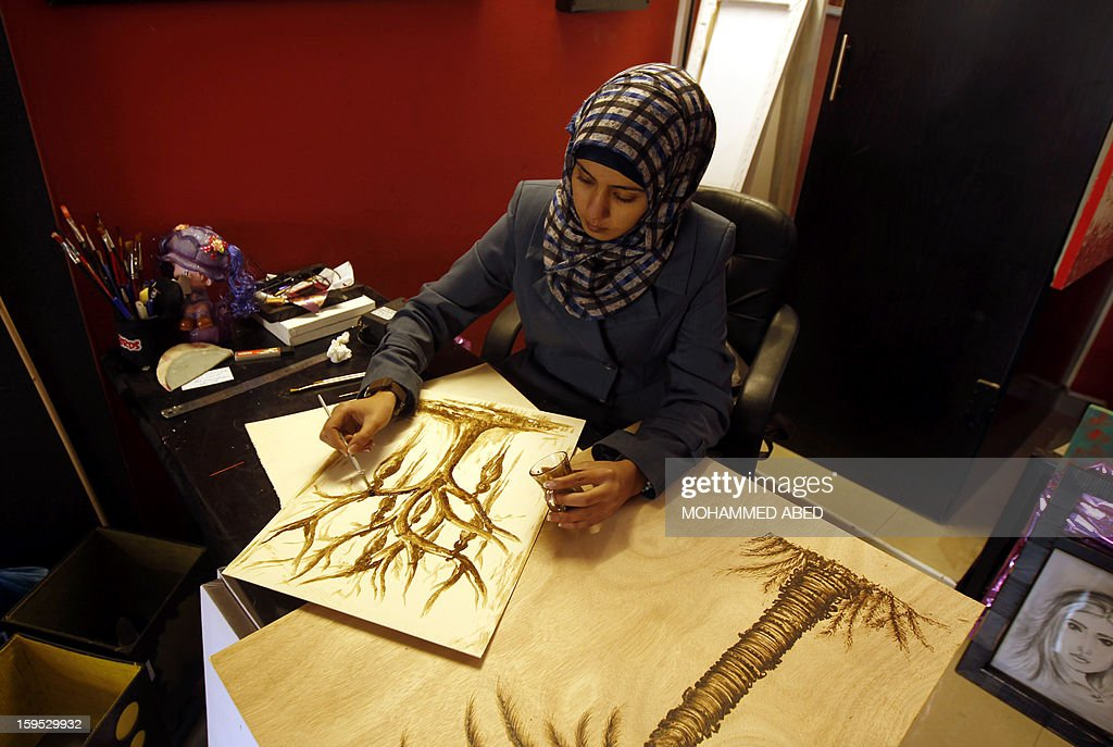 Palestinian artist Salwa Sbakhi paints using coffee at her studio in Gaza City on January 13, 2013. Salwa, who lives in the southern Gaza Strip, has studied fine arts at Al-Aqsa University in Gaza, and participated in numerous local exhibitions in an attempt to market her art. AFP PHOTO/MOHAMMED ABED