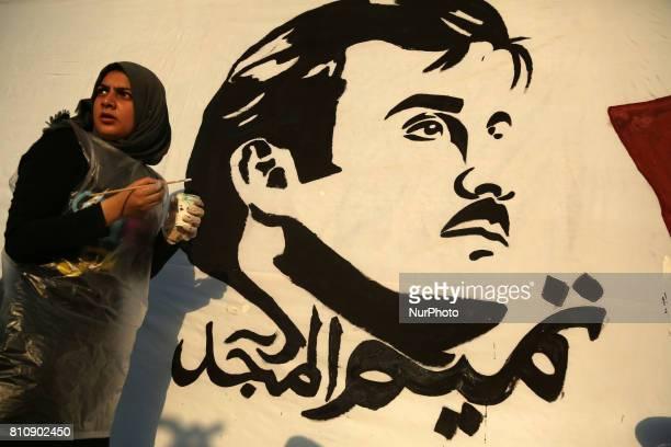 Palestinian artists draw on a wall bearing a portrait of Qatar's Emir Sheikh Tamim bin Hamad Al Thani which has become the symbol of Qatari...