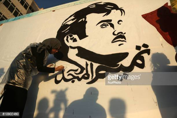 Palestinian artists draw on a wall bearing a portrait of Qatar's Emir Sheikh Tamim bin Hamad Al Thani which has become the symbol of Qatari...