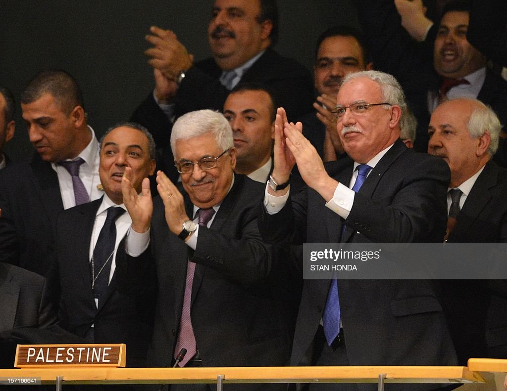 Palestinian Authority President Mahmoud Abbas (C) and the delegation celebrate after the United Nations General Assembly voted to approve a resolution to upgrade the status of the Palestinian Authority to a nonmember observer state November 29, 2012 at UN headquarters in New York. AFP PHOTO/Stan HONDA