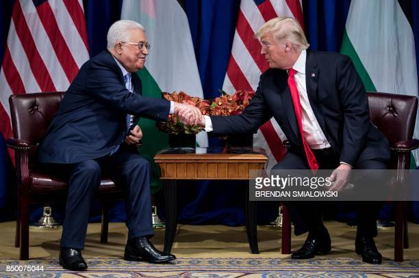 Palestinian Authority President Mahmoud Abbas and US President Donald Trump shake hands before a meeting at the Palace Hotel during the 72nd United...