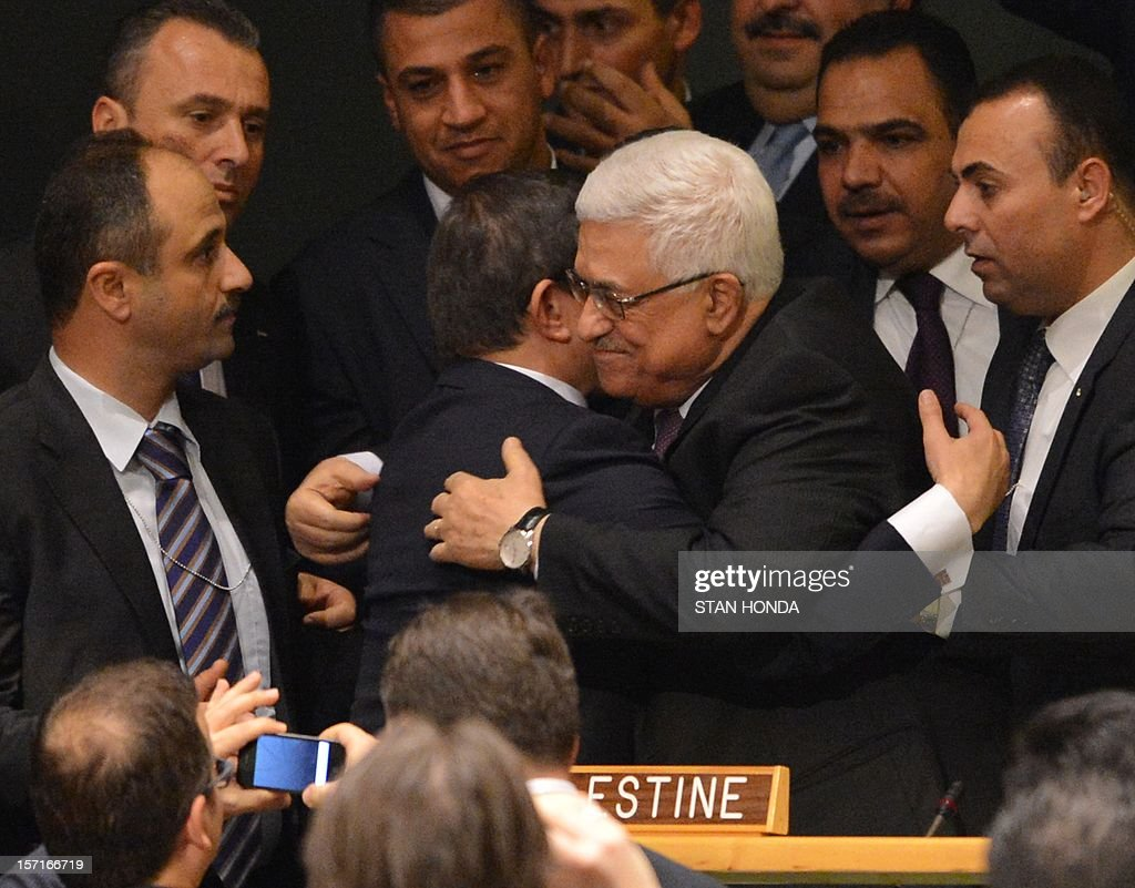 Palestinian Authority President Mahmoud Abbas (C) gets a hug from Ahmet Davutoglu, Turkey's Foreign Minister, as the Palestinians celebrate after the United Nations General Assembly voted to approve a resolution to upgrade the status of the Palestinian Authority to a nonmember observer state November 29, 2012 at UN headquarters in New York. AFP PHOTO/Stan HONDA