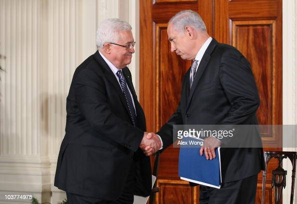 Palestinian Authority President Mahmoud Abbas shakes hands with Israeli Prime Minister Benjamin Netanyahu during an East Room statement at the White...