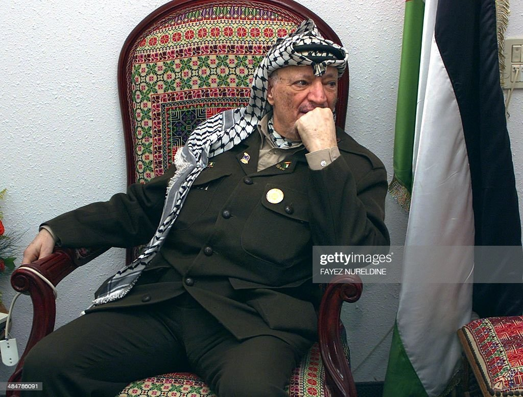 Palestinian Authority President Yasser Arafat listens to his aide brief him on the latest regarding the Israeli raid into the Gaza Strip during his...