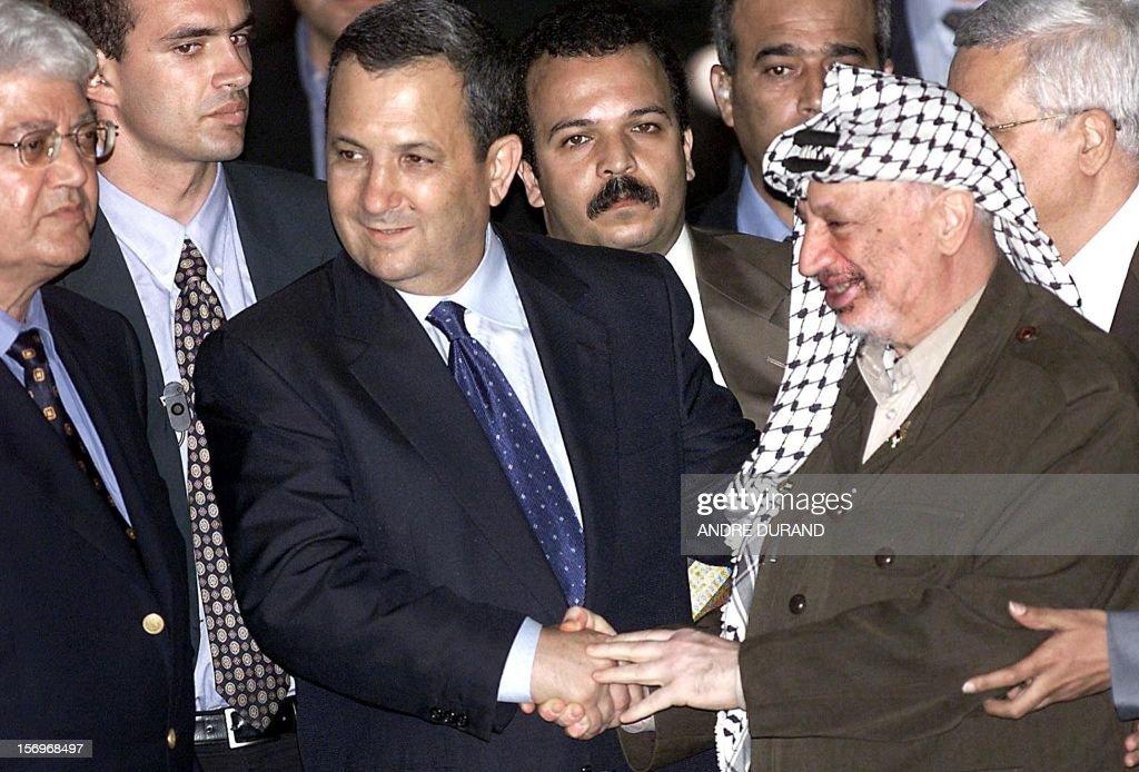Palestinian Authority President Yasser Arafat shakes hands with Israeli Prime Minister Ehud Barak while Israeli Foreign Minister David Levy looks on...