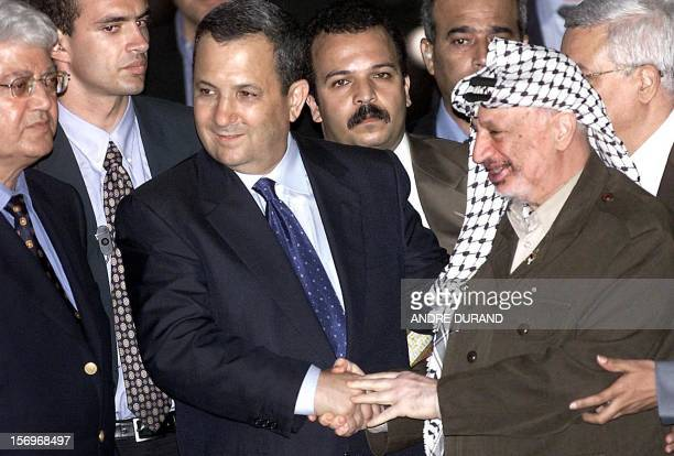 Palestinian Authority President Yasser Arafat shakes hands with Israeli Prime Minister Ehud Barak while Israeli Foreign Minister David Levy looks on...
