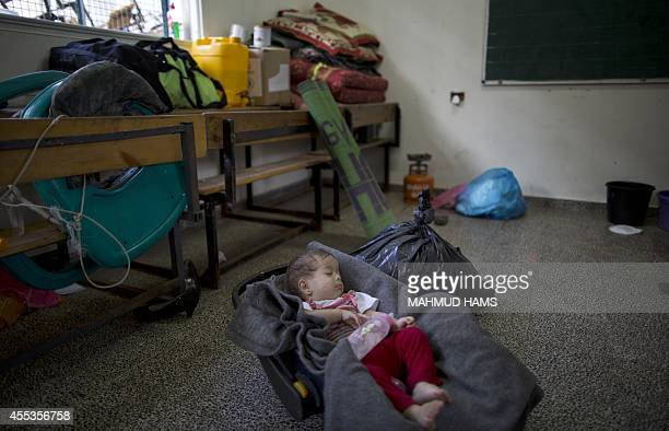 A Palestinian baby sleeps at a classroom at a United Nationsrun school in Gaza City on September 13 2014 one day before children go back to school...
