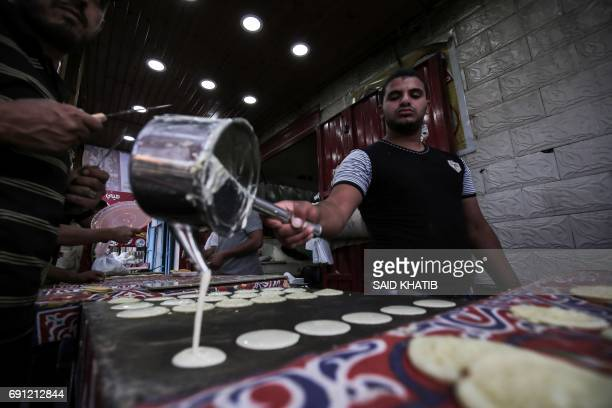A Palestinian baker prepares 'Qatayef' traditional pancakes that are popular during the Muslim fasting month of Ramadan in Rafah in the southern Gaza...