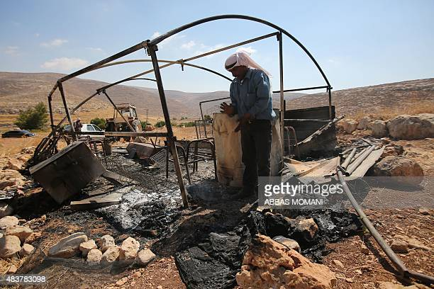 A Palestinian Bedouin checks a torched tent in Ein Samiya a village in the Israelioccupied West Bank on August 13 2015 after a reported attack by...