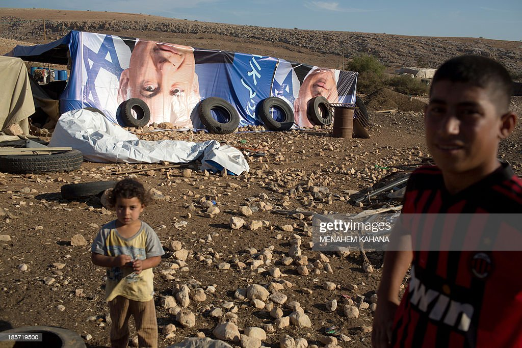 Palestinian Bedouin children stand in front of makeshifts tents covered with election posters depicting Israeli Prime Minister Benjamin Netanyahu on October 24, 2013 at a West Bank Palestinian Bedouin camp in the Jordan valley. KAHANA