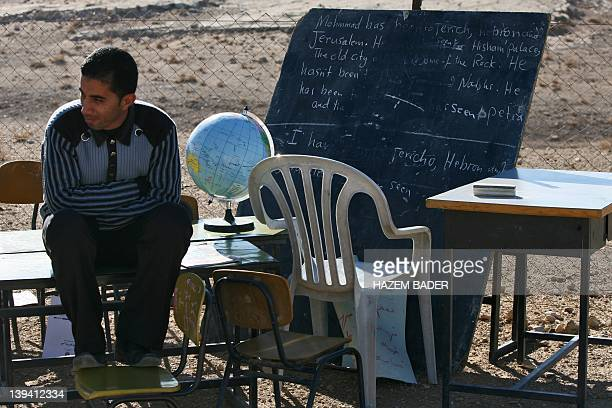A Palestinian Bedouin man sits amidst desks and equipment from a classroom which was destroyed at a Bedouin camp located in the village of Dakeka...
