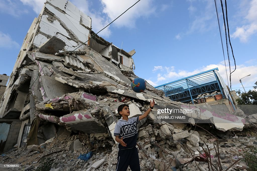 A Palestinian biy plays football outside the remains of his house on June 22, 2015 in Gaza City that was destroyed during 50-day war between Israel and Hamas-militants in the summer of 2014. A widely anticipated United Nations report said both Israel and Palestinian militants may have committed war crimes during last year's Gaza war, decrying 'unprecedented' devastation and human suffering.