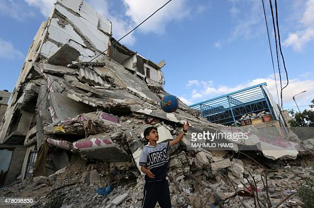 A Palestinian biy plays football outside the remains of his house on June 22 2015 in Gaza City that was destroyed during 50day war between Israel and...