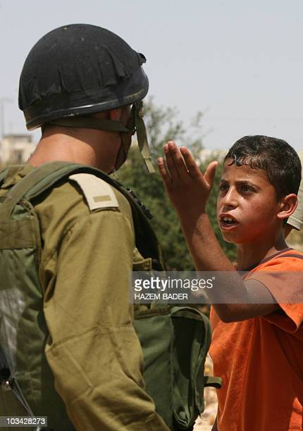 A Palestinian boy argues with Israeli border police during a demonstration against the settlement of Karmi Tsor near Beit Omar village outside the...