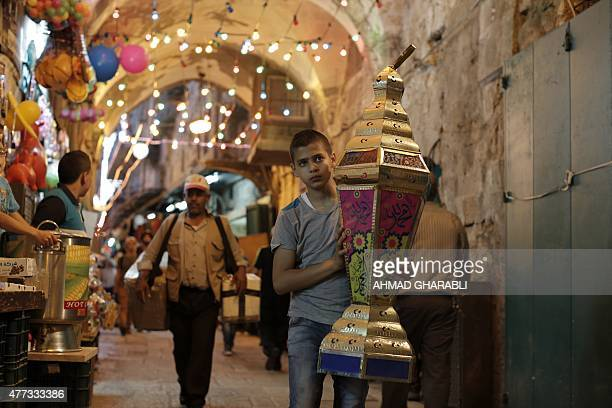 A Palestinian boy carries a lantern walking past decorated shops at the entrance of the AlAqsa mosque compound in the old city of Jerusalem on June...