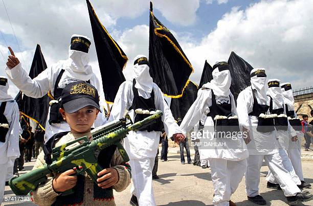 Palestinian boy carries a toy weapon as Islamic Jihad supporters dressed as suicide bombers take part in a demonstration against Israel in the...