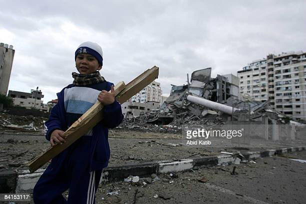 Palestinian boy carries pieces of wood found amongst the rubble of a destroyed Education Ministry building after an Israeli air strike in Gaza Gaza...