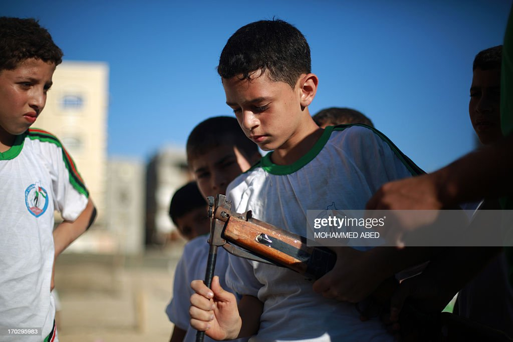 A Palestinian boy checks an airsoft hunting rifle during a summer physical training camp run by Hamas during their summer vacation in Gaza City on June 10, 2013.