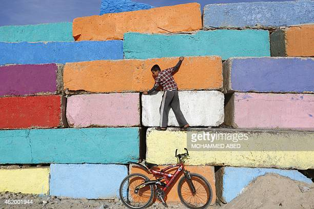 A Palestinian boy climbs a big stone wall on January 23 2015 that was painted by local artists at the sea port in Gaza City in an attempt to bring...