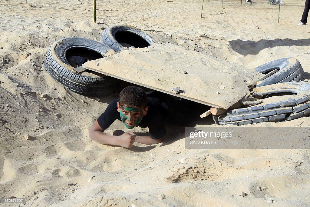 A Palestinian boy crawls on the sand during training at a military-style summer camp being held by the Islamic Jihad movement during the youngsters' summer school vacation in Rafah town, in the southern Gaza Strip, on June 12, 2013. Thousands of youngsters between the age of six and 16, can participate in the summer camp where they receive military as well as religious training.